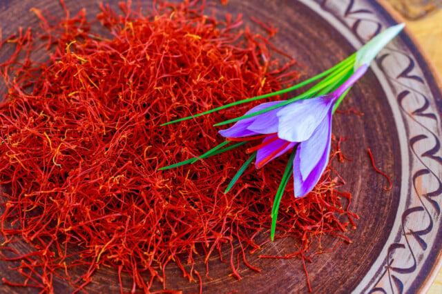 dried saffron pistils and saffron flower in a bowl